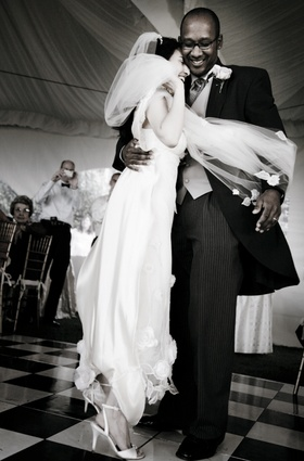 Bride in a Claire Pettibone lace gown and veil dances with groom in black tails