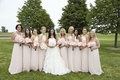 Bride in Oscar de la Renta wedding dress with bridesmaids in Amsale pink dresses