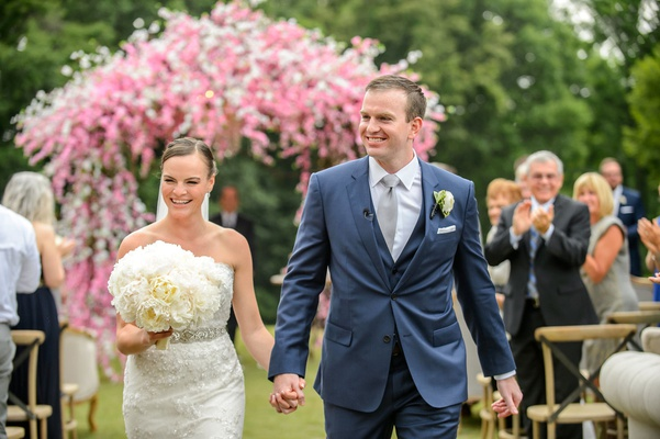 Bride in strapless wedding dress holding groom in blue suit hand white peony bouquet pink chuppah