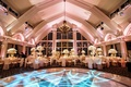 Oval dance floor with blue lighting, chandelier, gold and white centerpieces at ballroom reception