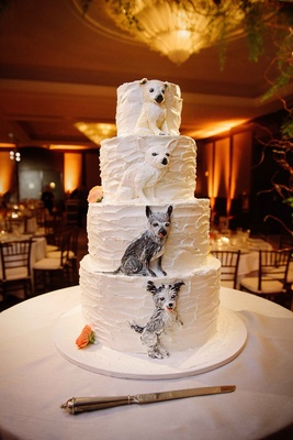 White four layer wedding cake with buttercream frosting dog replica designs on each tier orange
