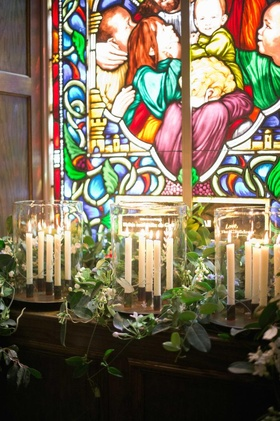 Church wedding ceremony with candles and stained glass