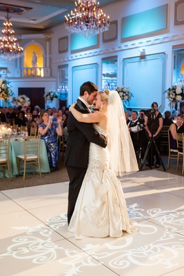 Bride with hip-length veil dancing with groom