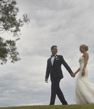 Couple holding hands in wedding attire on grass