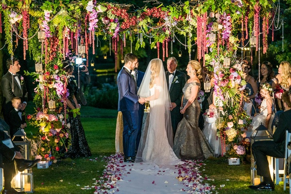 Bride in anne barge wedding dress with groom in navy suit under greenery chuppah with flowers