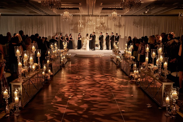 Ivory drapery and chandeliers over altar area, patterned lighting on aisle, mirrored details