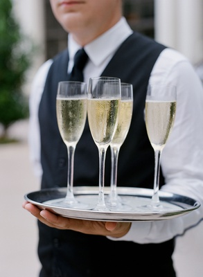 wedding reception cocktail hour silver tray four glasses of champagne vest server