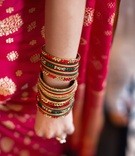 Indian Bride-to-be wears bangle bracelets with yellow, green, red rhinestones
