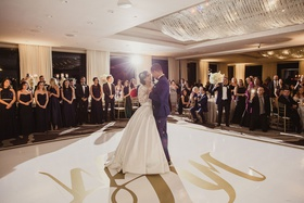 Bride in ball gown pnina tornai with groom first dance on dance floor guests watching in ballroom