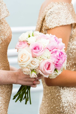 bridesmaid in gold holds bouquet with pink and ivories roses, pink peonies