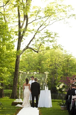 Bride in a Romona Keveza dress with groom in a black tuxedo in an outdoor wedding ceremony