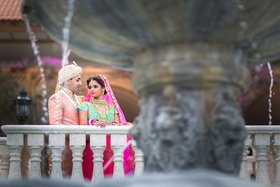 Indian-American bride in pink and turquoise lehenga, groom in traditional outfit