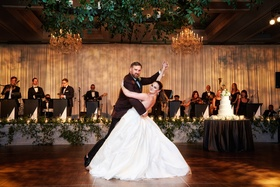 Bride in ball gown wedding dress with groom in burgundy suit dip during first dance live band