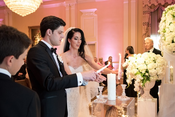 Bride and groom lighting candle during unity candle ceremony at Dallas wedding