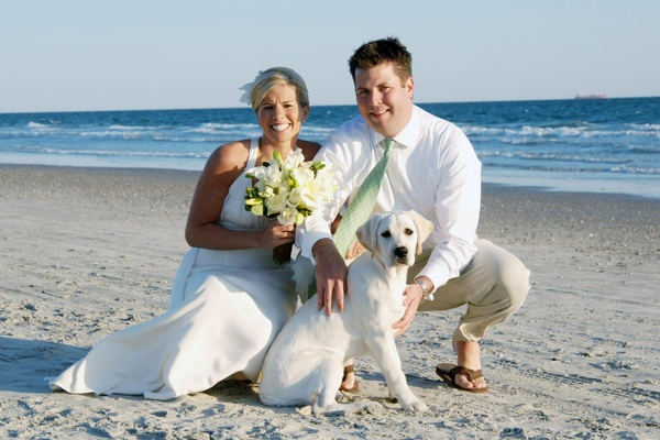 Bride and groom on beach with white lab puppy