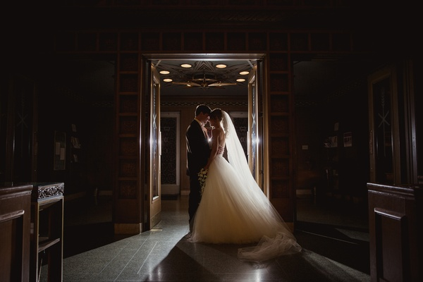 bride in mira zwillinger wedding dress with mark ingraham overskirt with groom in tux, backlit