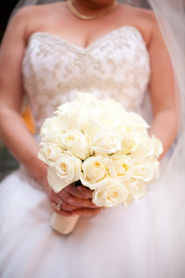 Bride holds bouquet with dozens of ivory roses