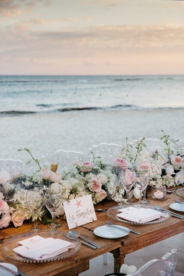 Beach wedding reception with wood head table with floral runner facing the water