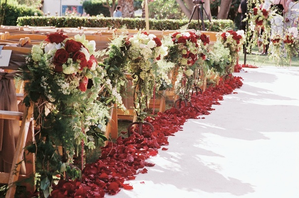 White aisle runner with red rose petals and flowers on wooden chairs