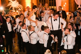Bride and groom in chairs during wedding reception hora dance jewish wedding tradition