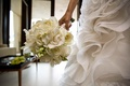 bride carries bouquet next to ruffled skirt