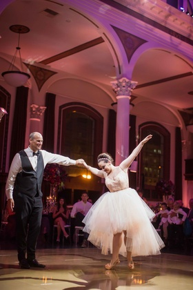Bride performing father-daughter dance in high heels with high low skirt for reception dress