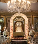 Flower arch and petal aisle under crystal chandelier