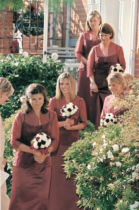 bridesmaids wear burgundy dresses and carry white and red bouquets