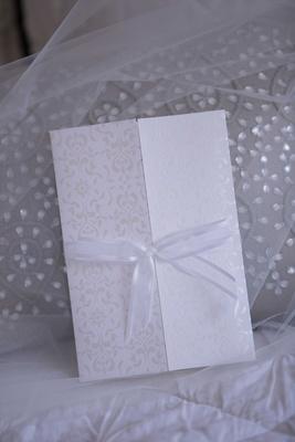 Damask print white cream wedding invitation gate fold with sheer white bow on veil