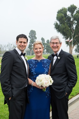 Mother of groom in royal blue dress with floral vine print bateau neckline white bouquet tuxedos