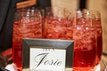 red specialty cocktail on ice in highball glass for guests at wedding