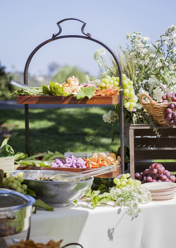 fresh fruit station spread grapes leaves white wildflowers wooden plates food reception