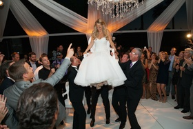 Guests in formal attire lifting bride in chair