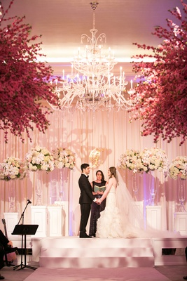 indoor ceremony, chandelier above bride and groom exchanging vows,