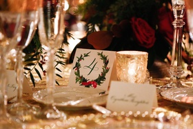 Red and green holly wreath design with calligraphy number on table card
