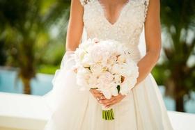 Bride in Carolina Herrera v-neck wedding dress holding bouquet light flowers white pink rose peony