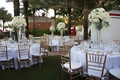 wedding reception with round white tables gold chairs tall centerpieces rose hydrangea flowers