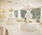 Ballroom white and gold wedding reception decor white flower arrangements gold chairs chandeliers