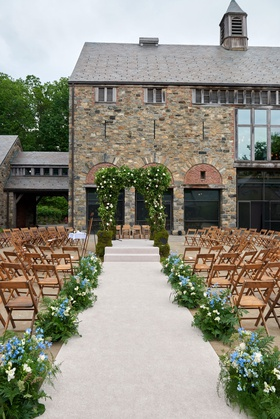 wedding guests seated in the round new york farm venue blue flowers greenery wood chairs stone venue