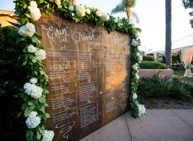 wedding reception wood seating chart sign white calligraphy greenery white hydrangea flowers