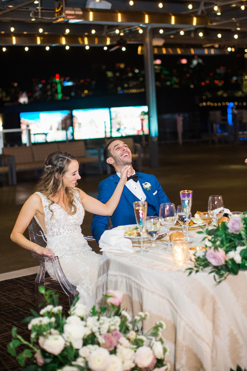 bride in lace dress and groom in bright blue suit laughing while sitting at their sweetheart table