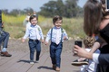 wedding ceremony outdoor ring bearers in navy blue slacks pants light blue shirts pink tie suspender