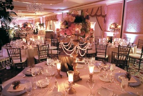 Ballroom with pink lighting and lavender and pink centerpieces