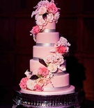 Pink cake with silver ribbon and sugar flowers