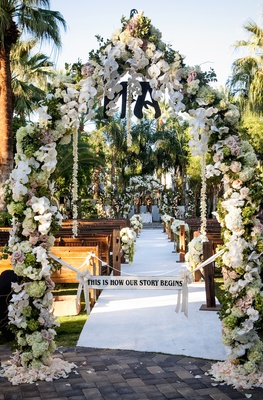 "Flower arch with ""This is How Our Story Begins"" sign"