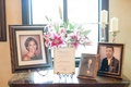 Wedding cocktail hour reception table with photos of late loved ones deceased with sign and lilies
