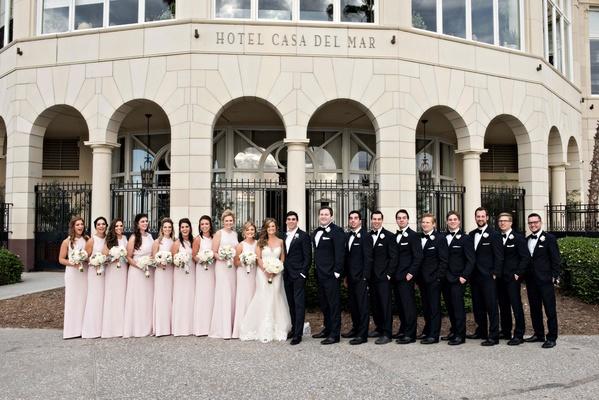 Wedding party pink bridesmaid dresses groomsmen in tuxedos in front of Casa Del Mar in Santa Monica