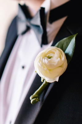 ranunculus boutonniere ivory on tuxedo lapel of groom in bow tie