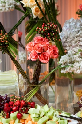 Wedding reception with roses and hydrangeas in cylinder vases decorating a fruit table