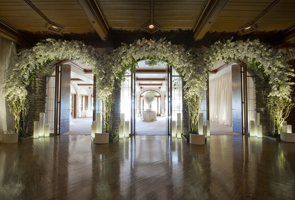 Three flower arches at entrance to escort card table